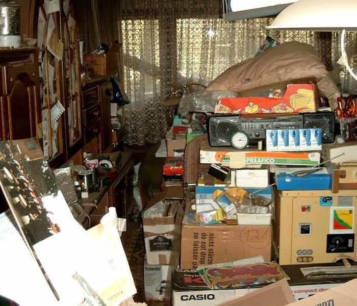 picture of inside of home with piles of clothing, belongings, furniture and things everywhere.