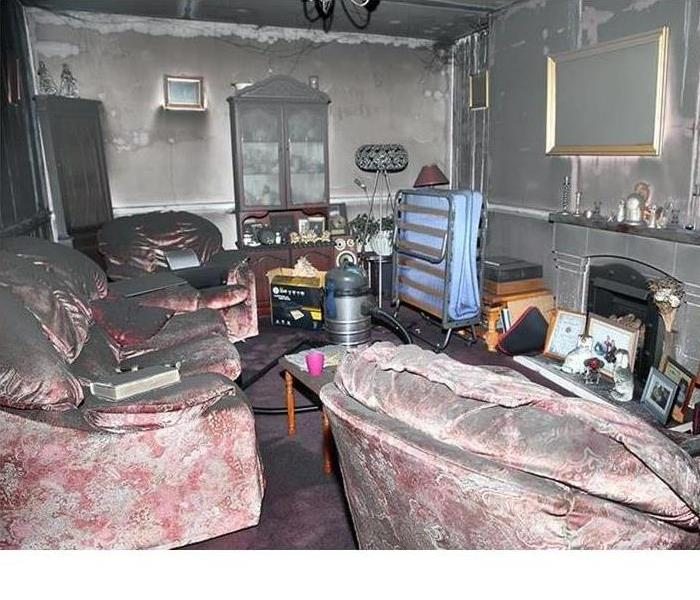 Picture of a living room with sofas covered in fire soot, the walls covered in soot and burn marks as well as the walls.